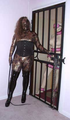 A photo of Evil Dolly in zentai standing next to her cage.